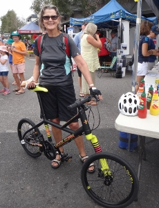 Mature female rider with small-wheeled bike at a community event