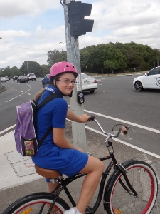 Girl riding to school on a cruiser bike